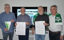 VfL Vorstandsmitglieder Hans Hößler u Wolfgang Keusch umrahmt von EMB-Geschäftsführern Detlef u. Dieter Meier mit den Spielplänen des EMB-Cups 2019